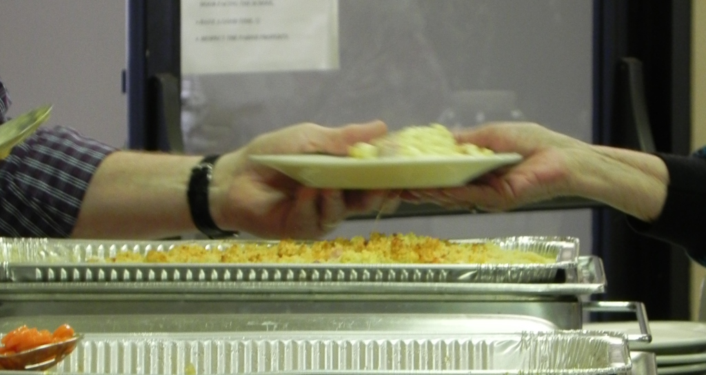 A volunteer serving a woman a plate of hearty food
