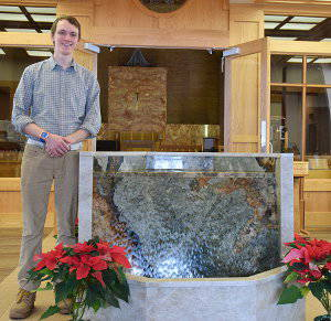 Jake Nelson stands next to new St. Michael baptismal font
