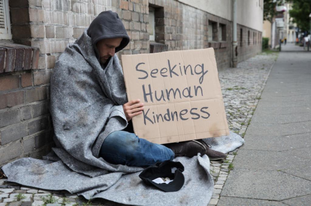 "A man holding a sign ""Seeking human kindness"""