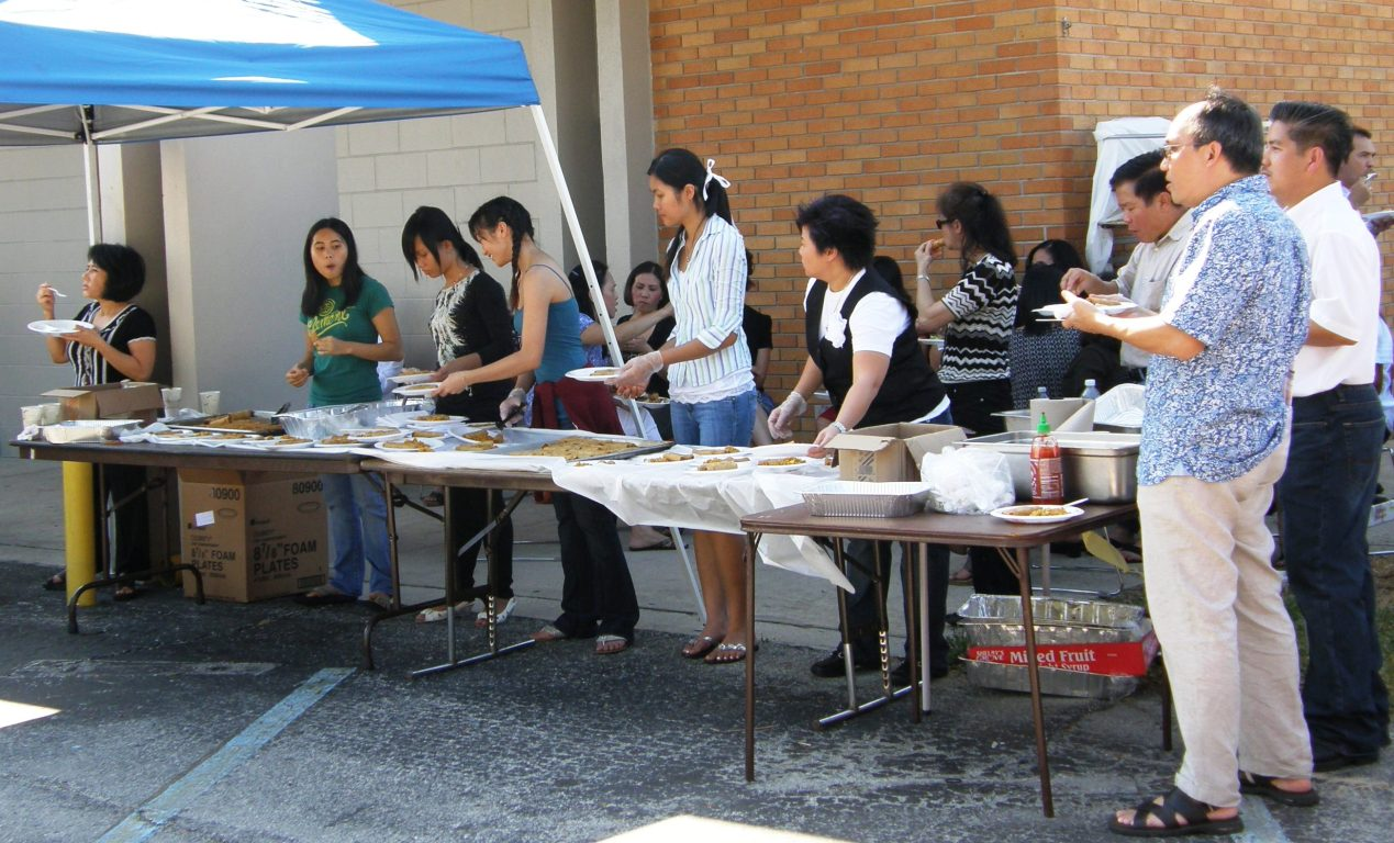 Vietnamese Community fills orders for egg rolls at the parish picnic.