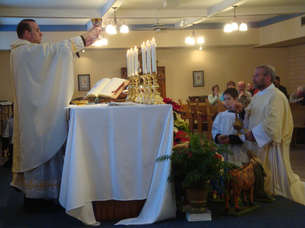 Father Joel elevates the chalice, with the Deacon Tom offering incensation.