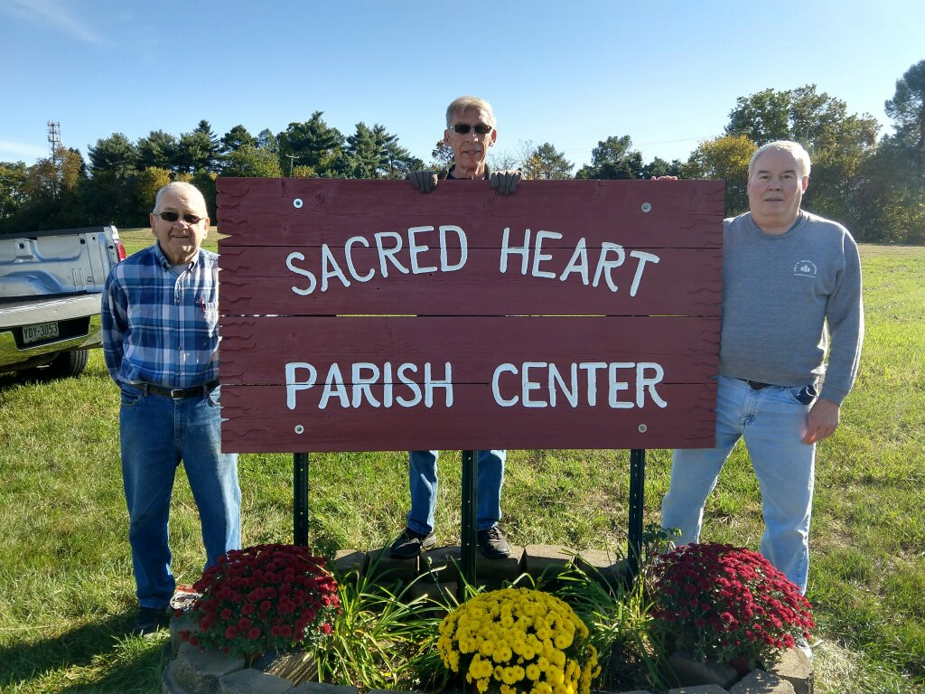 Paul Wivell, Jim Hobday and Bob Strine place the freshly painted sign at the Parish Center