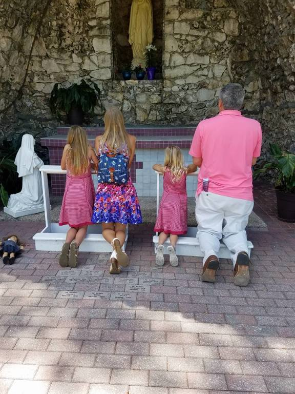 family praying together in Grotto